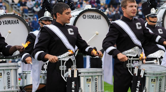 The snare drum line for the UConn Marching Band performing with fire sticks